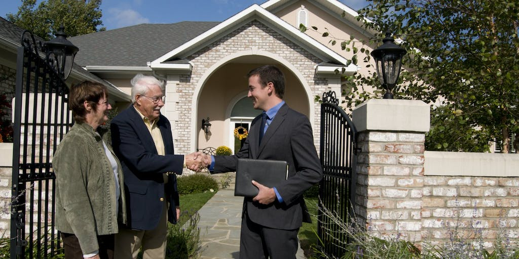 Estate agent showing new house to elderly couple