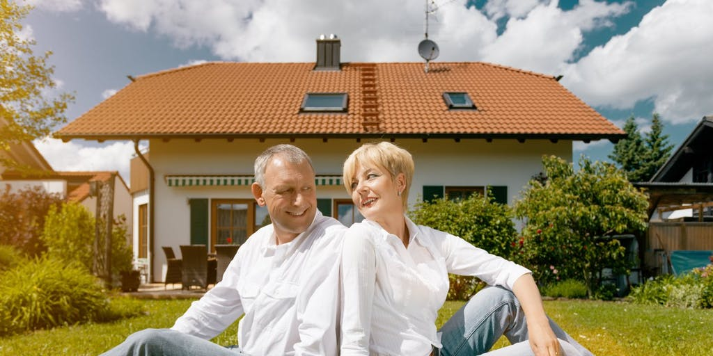 couple sitting in garden outside their house