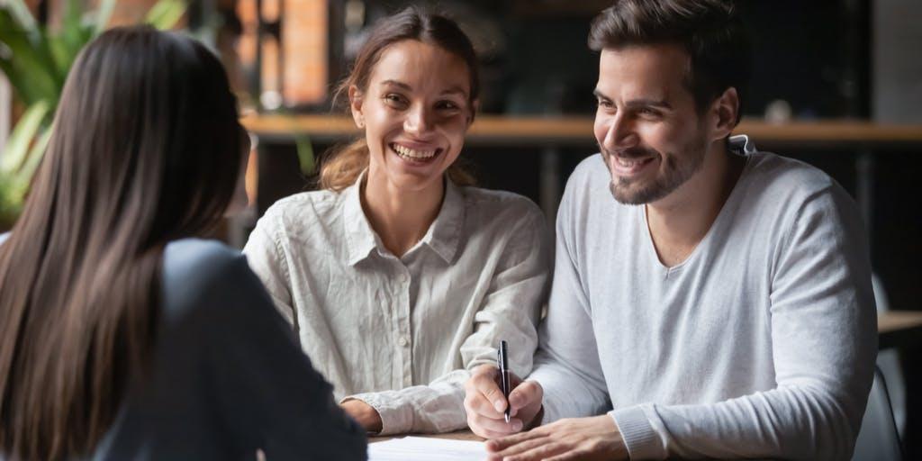 Smiling couple signing documents