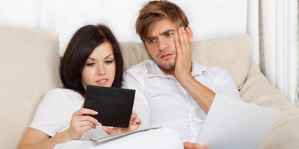 Man and woman on sofa looking at tablet