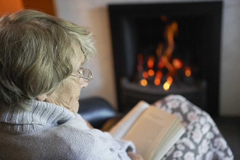 Elderly woman warm by the fire
