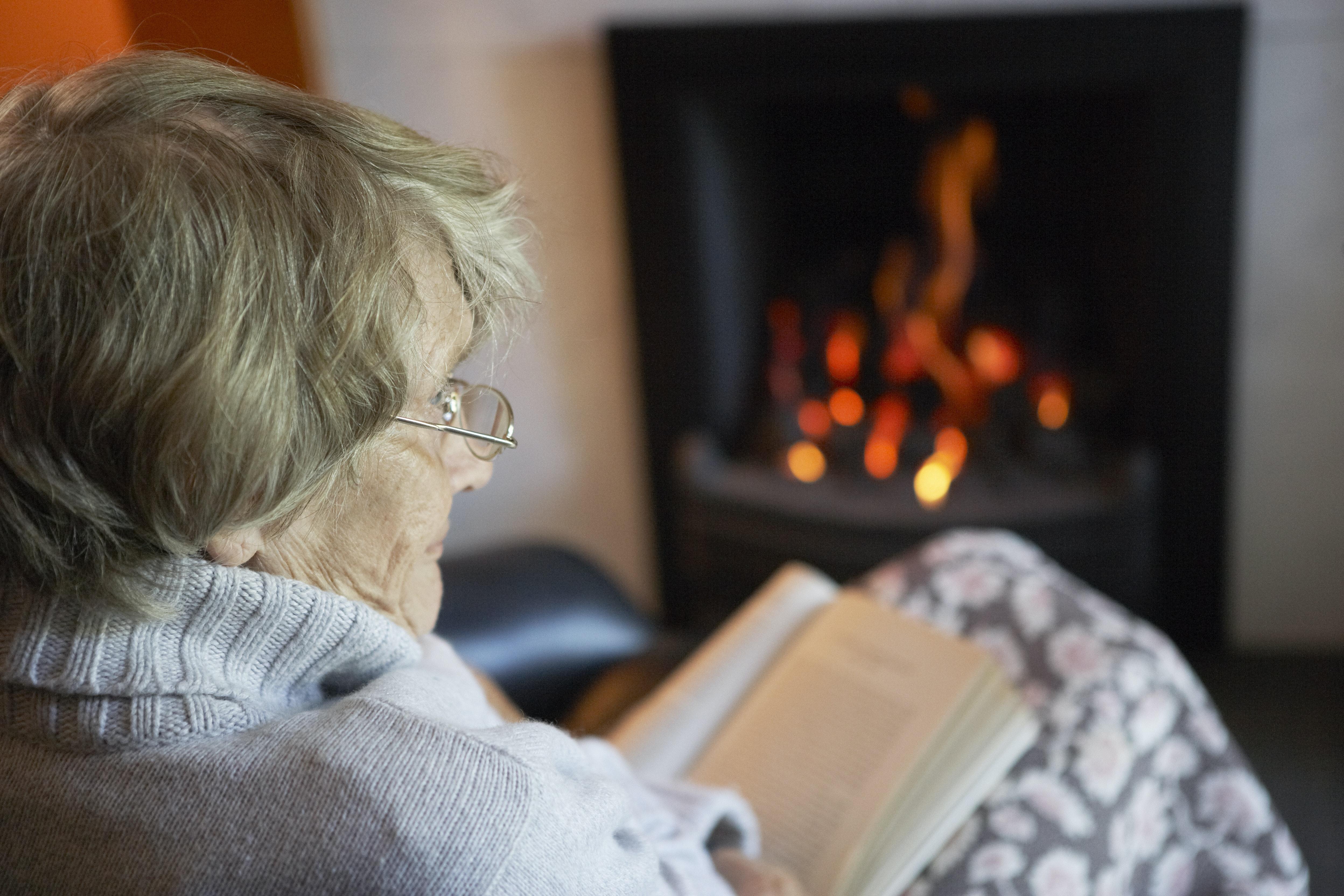 Elderly woman warm by the fire