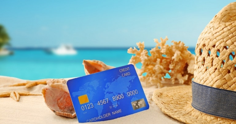 credit card on the beach by shells, coral and a hat