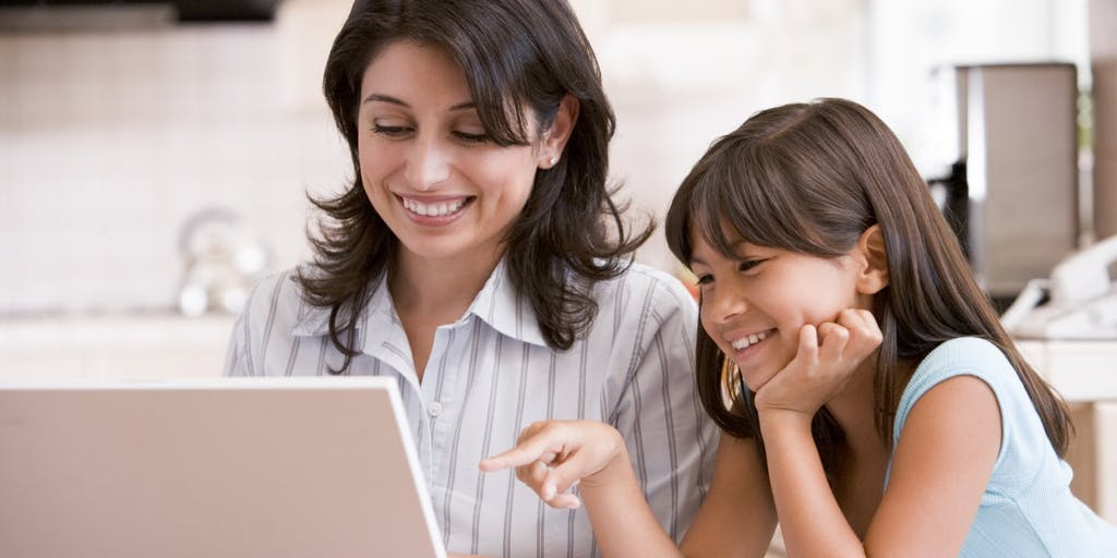 Woman and young girl looking at laptop