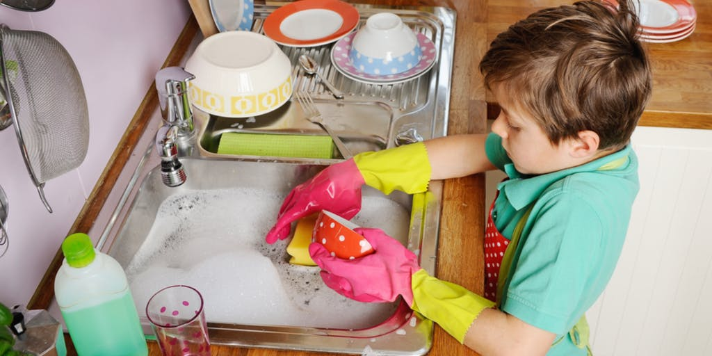 Little boy doing the dishes wearing rubber gloves