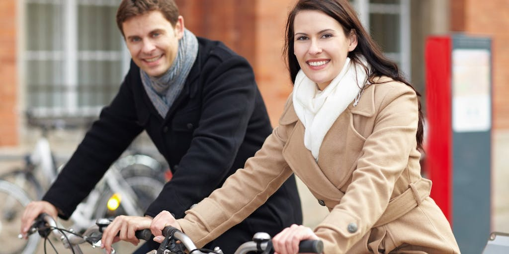 couple cycling side by side along the street