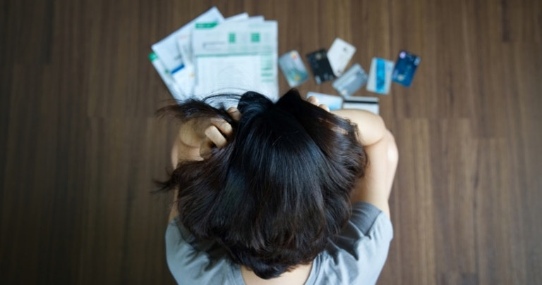 Woman looking at papers and credit cards on the floor, whilst gripping her name.