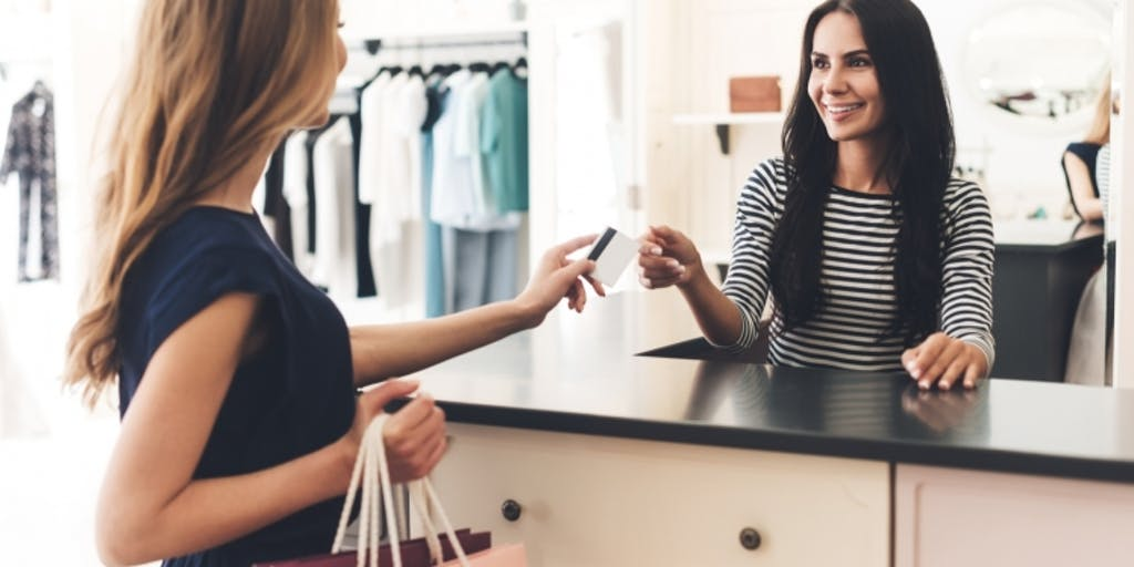 One woman giving her credit card with her right to another over the counter in a clothes shop.