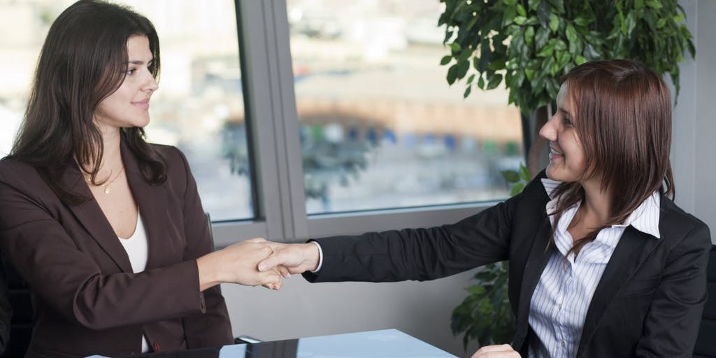businesswomen-at-desk-handshake-office
