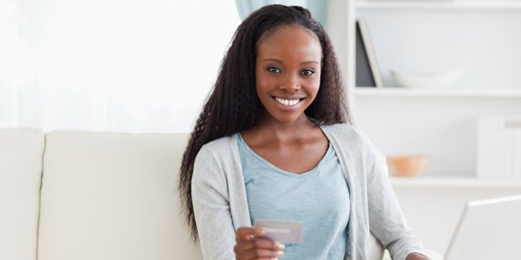woman on sofa with credit card and laptop