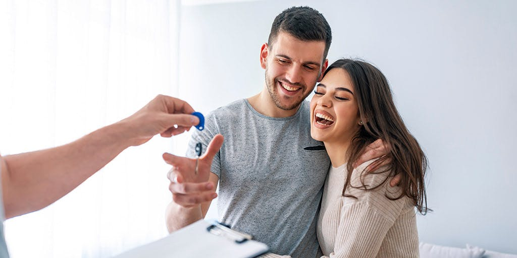 Young couple taking keys of their new house from broker.
