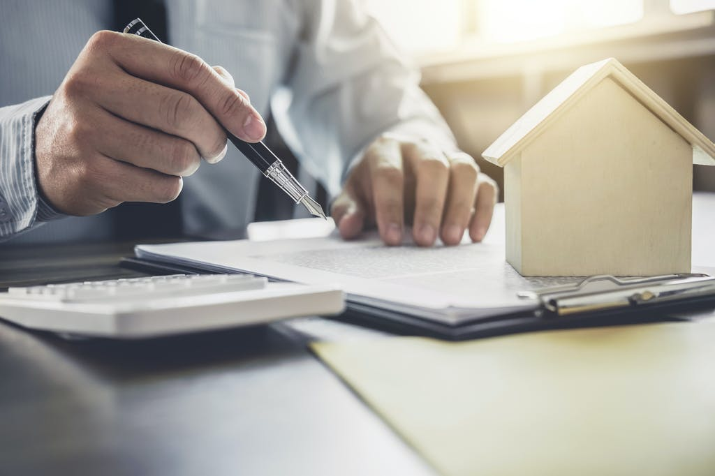 Image of a person doing paperwork with a model of a house on their clipboard.