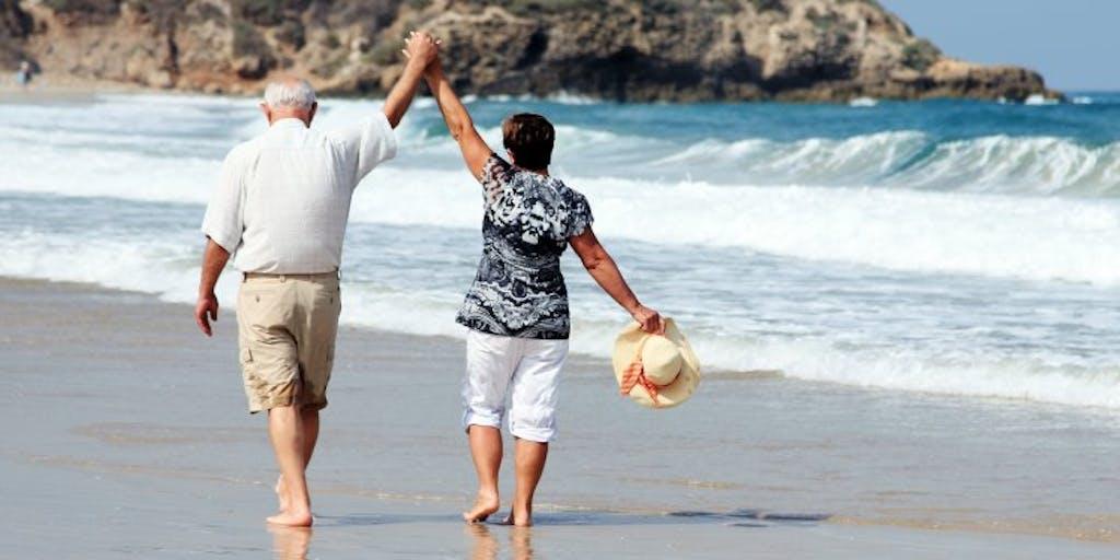 senior-couple-walking-on-the-beach