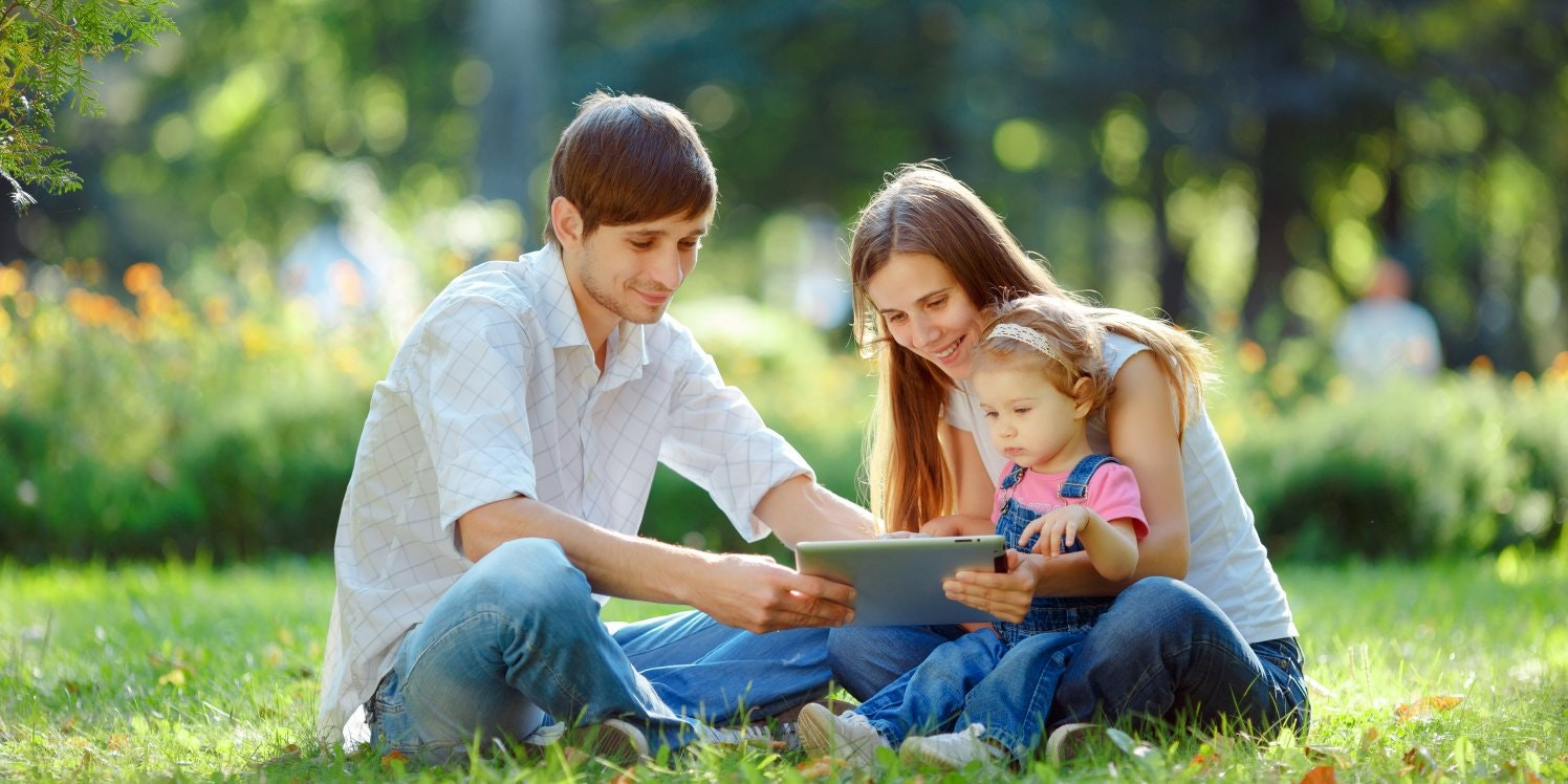 family-in-park-with-ipad-tablet
