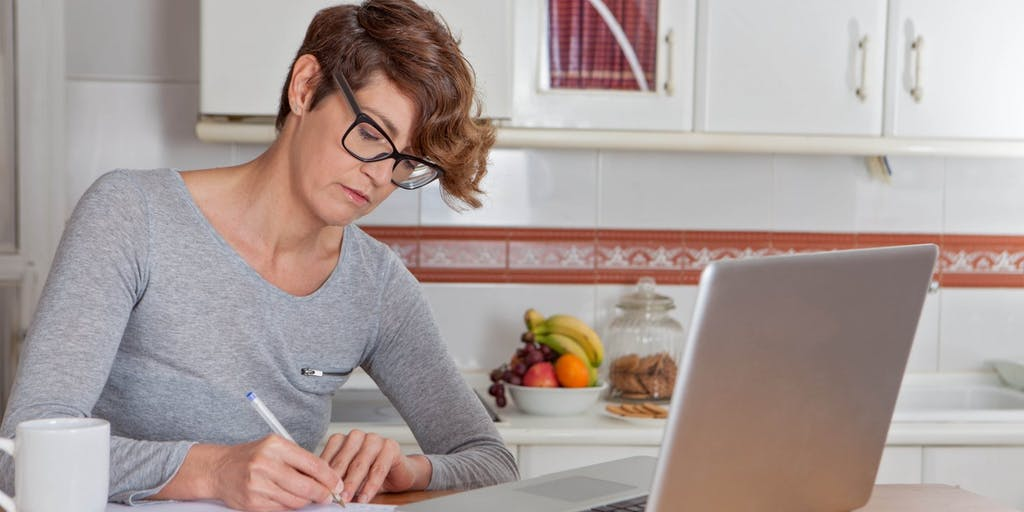 Women doing paperwork in her kitchen