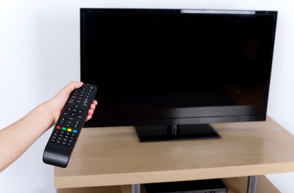Person pointing remote control at television to turn it off, rather than leaving it on standby