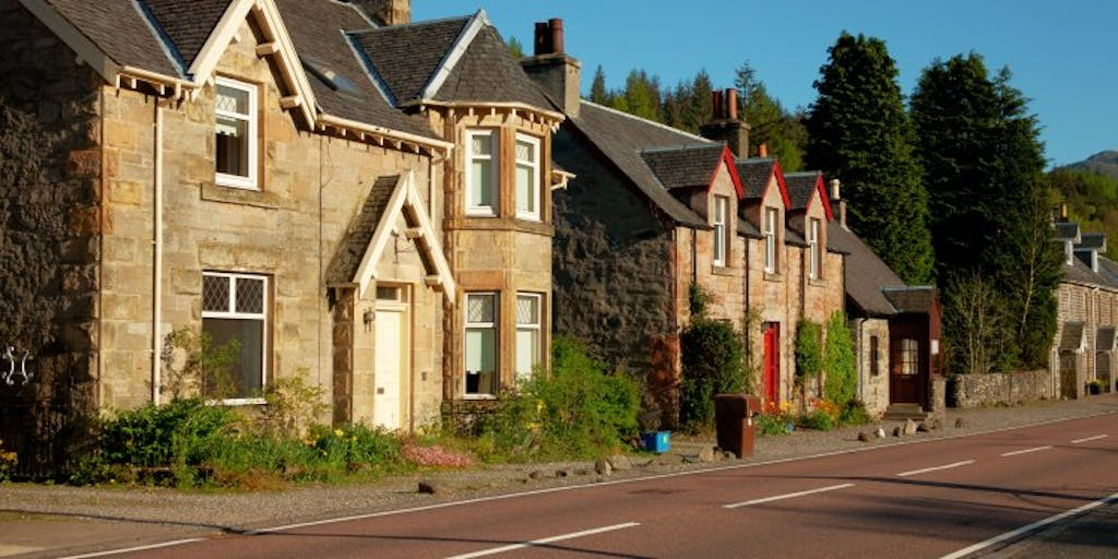 2 Scottish houses by a road. One house has a white door and the other has a red door.