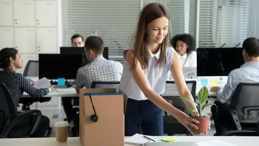 Smiling hired female company employee unpacking box with personal belongings