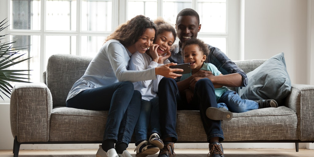 happy family on a sofa looking at a mobile device