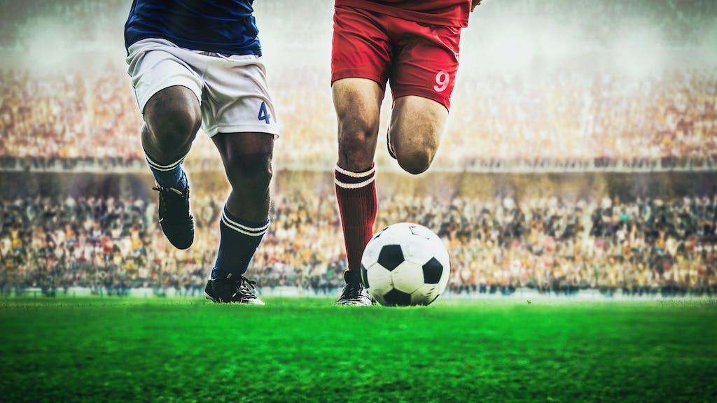 Footballers kicking ball