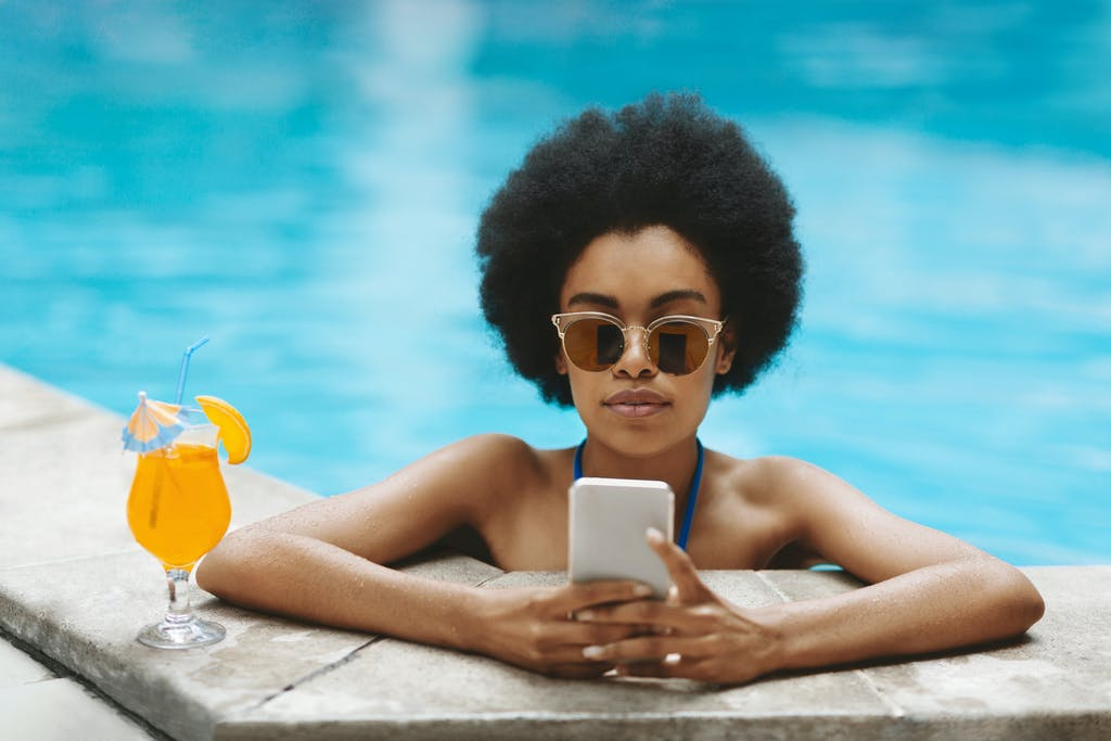 Woman using phone on holiday in pool
