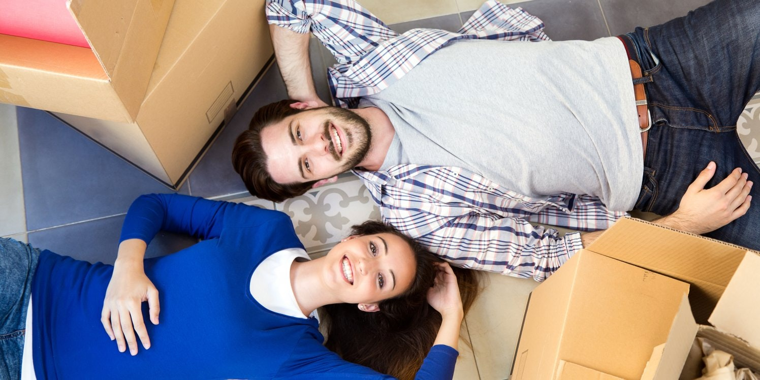 Young couple lying among packing boxes