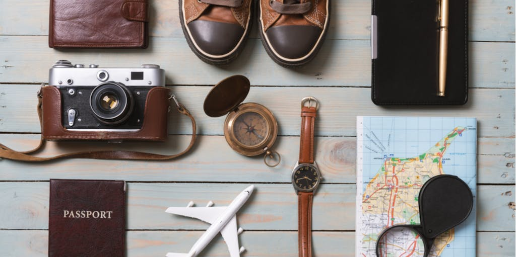 Set of traveler essentials on wooden background. Travel and adventure concept