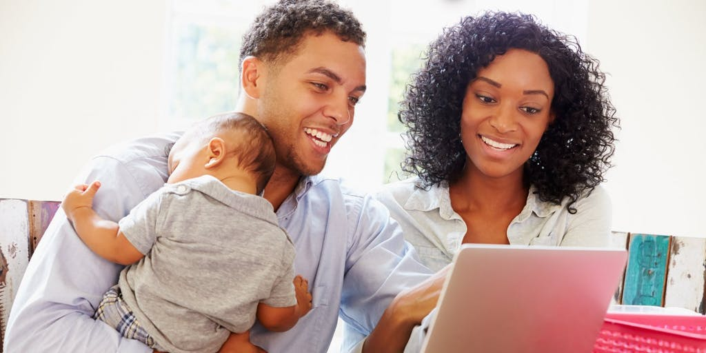 Couple with baby using laptop