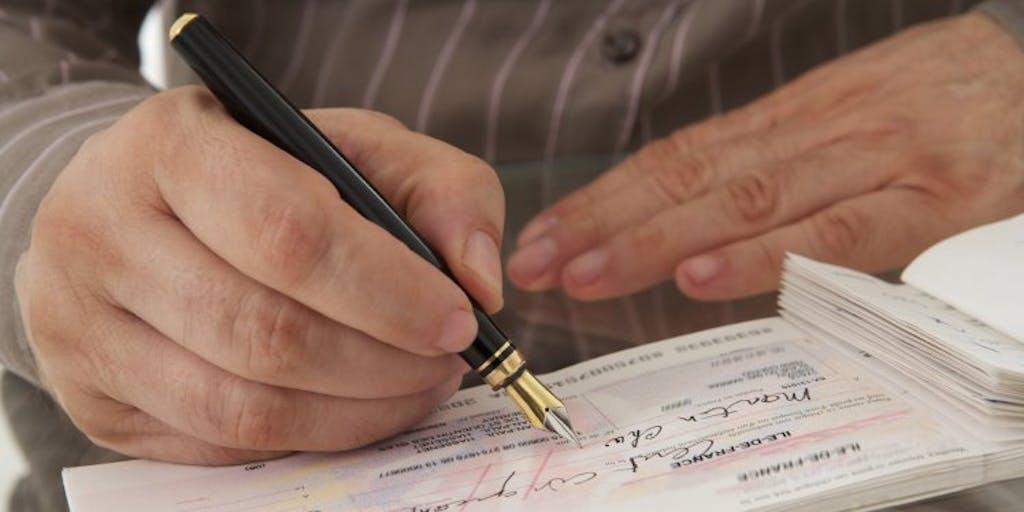 a-man-writes-a-cheque