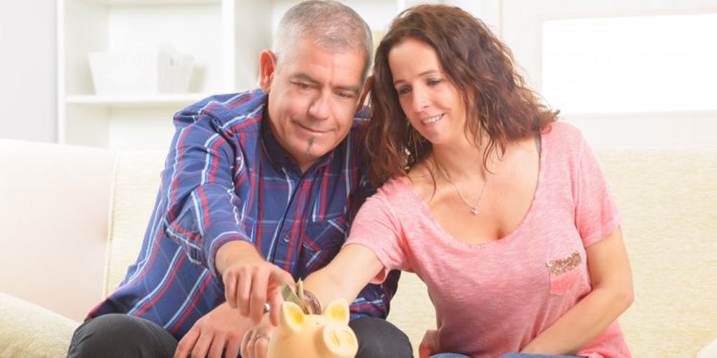 man-and-woman-putting-cash-in-piggy-bank
