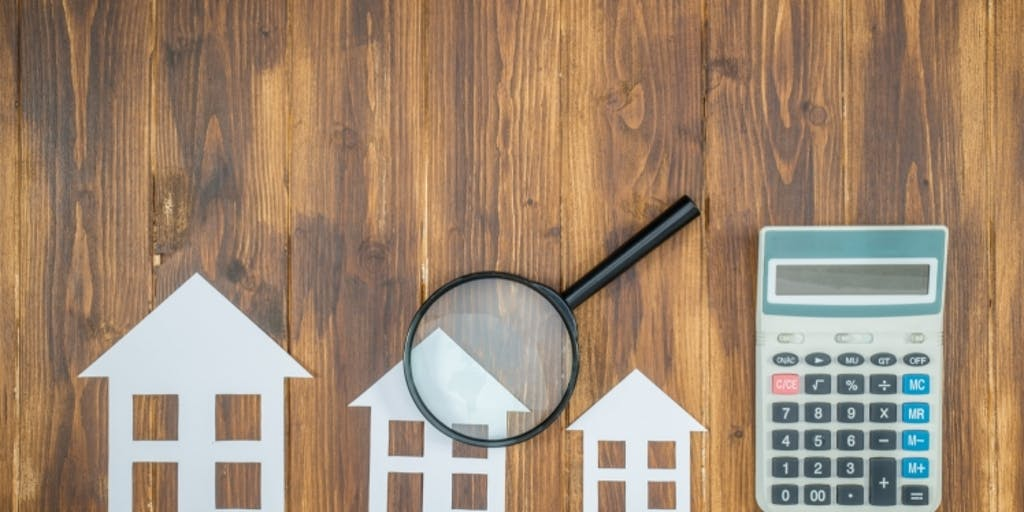 Paper houses, a magnifying glass and a calculator on a table looking down from above.