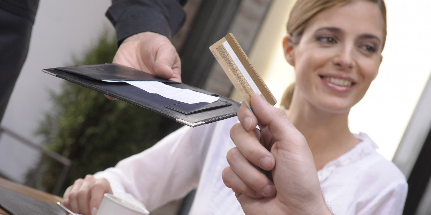 Couple paying bill in a restaurant with card.