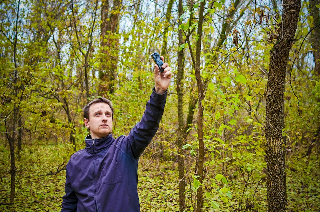 Man trying to find mobile coverage in woods