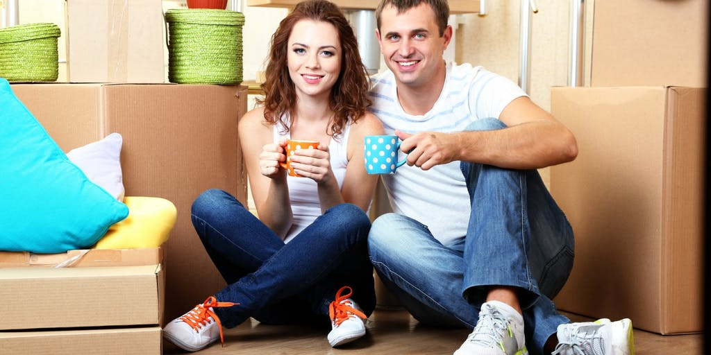 Young couple among packing boxes holding coffee mugs