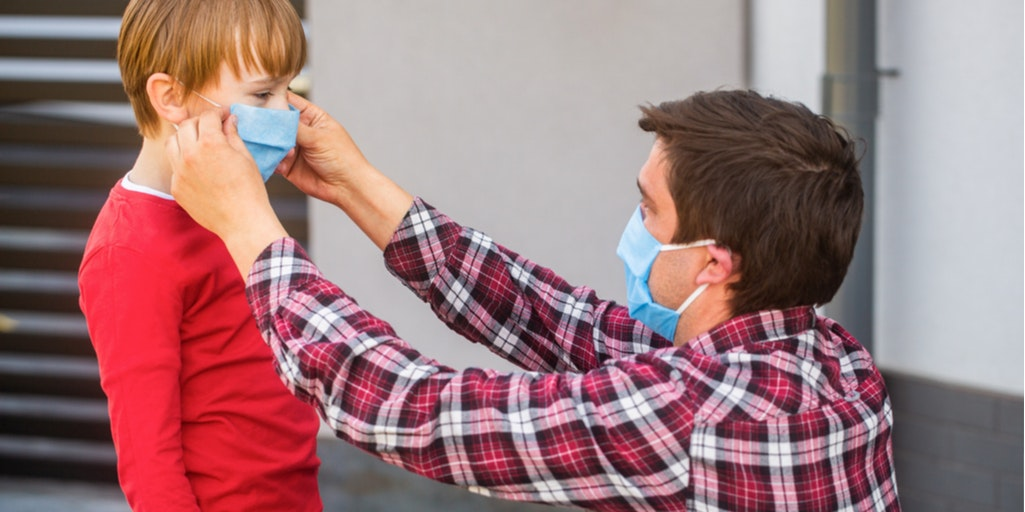 Man wearing a blue face mask and checkered shirt placing a mask on boy in red jumper