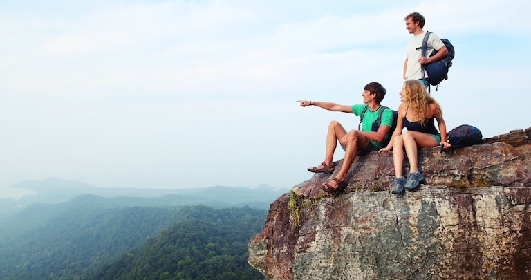 three travellers standing on a cliff