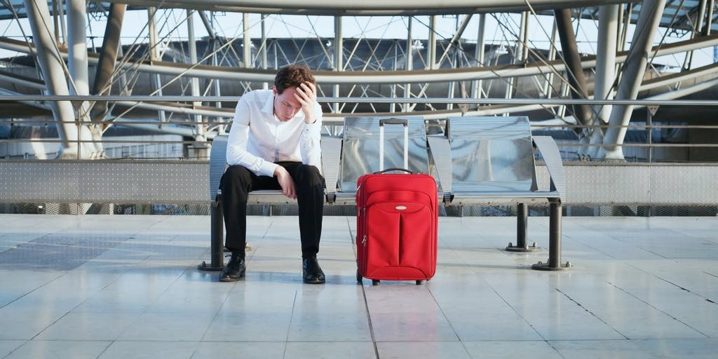Stressed man with luggage sitting on bench at airport