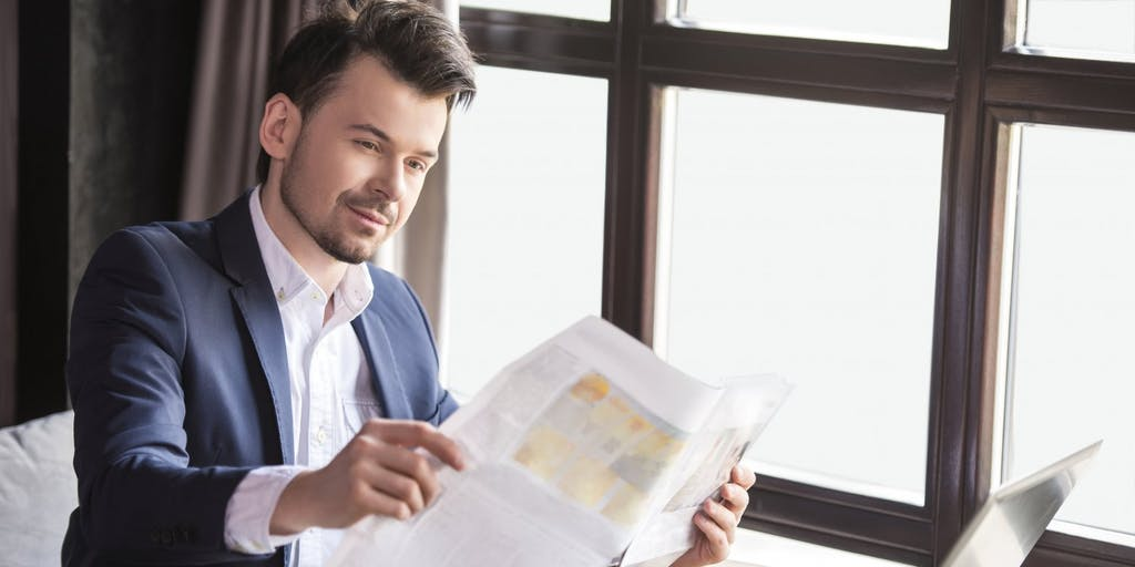 businessman-with-financial-newspaper-and-laptop