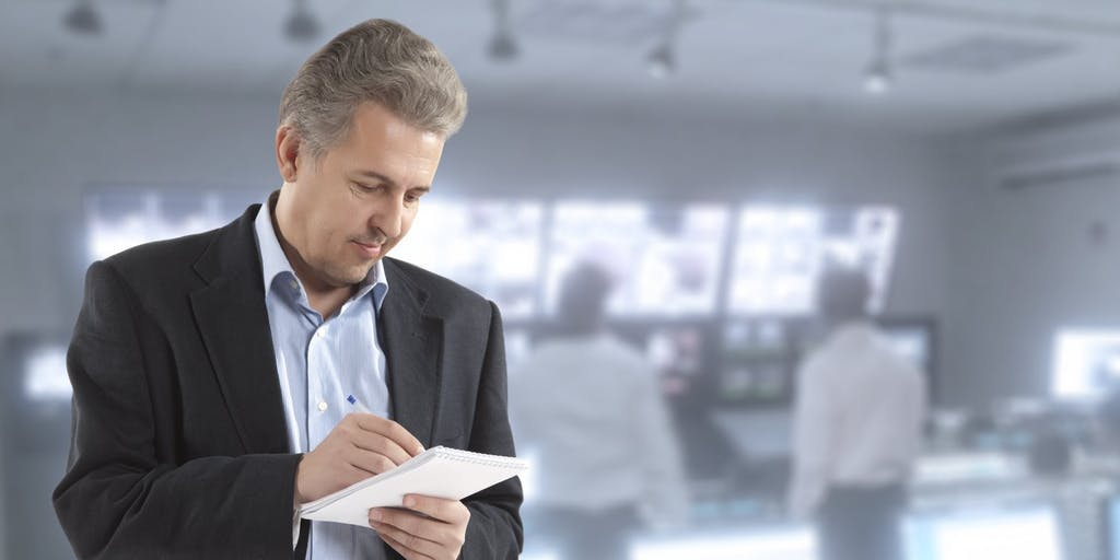 Man writing notes on notepad