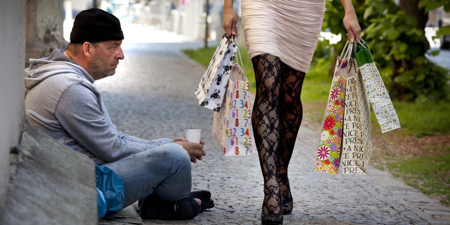 Woman with shopping bags walks buy homeless man