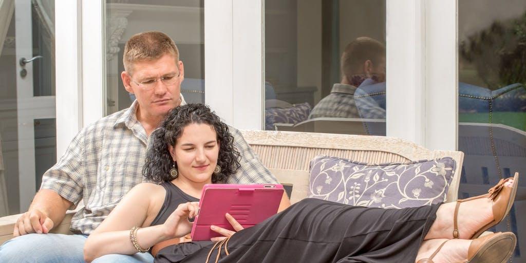 Couple looking at tablet in veranda