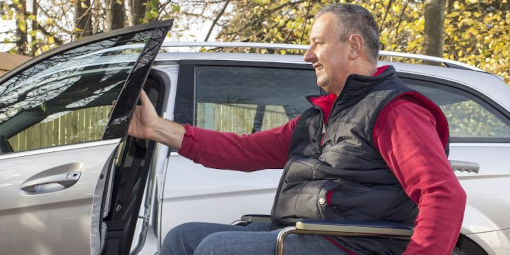 Man in a wheelchair wearing a red jumper and black gilet, opening the door of a car.