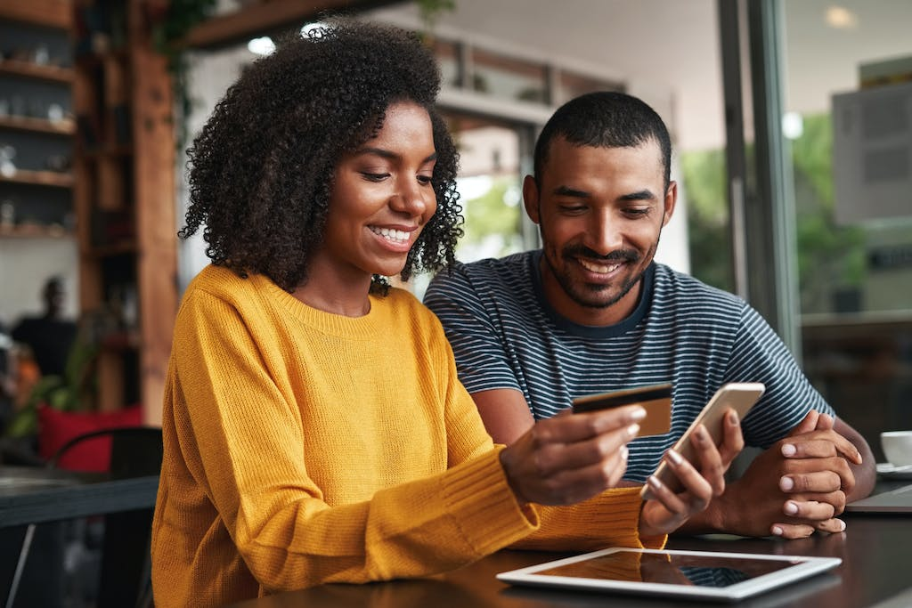 Black woman with boyfriend using credit card to shop online
