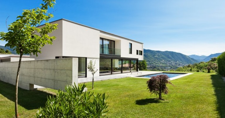 Modern villa with a garden and a pool in sunny weather.