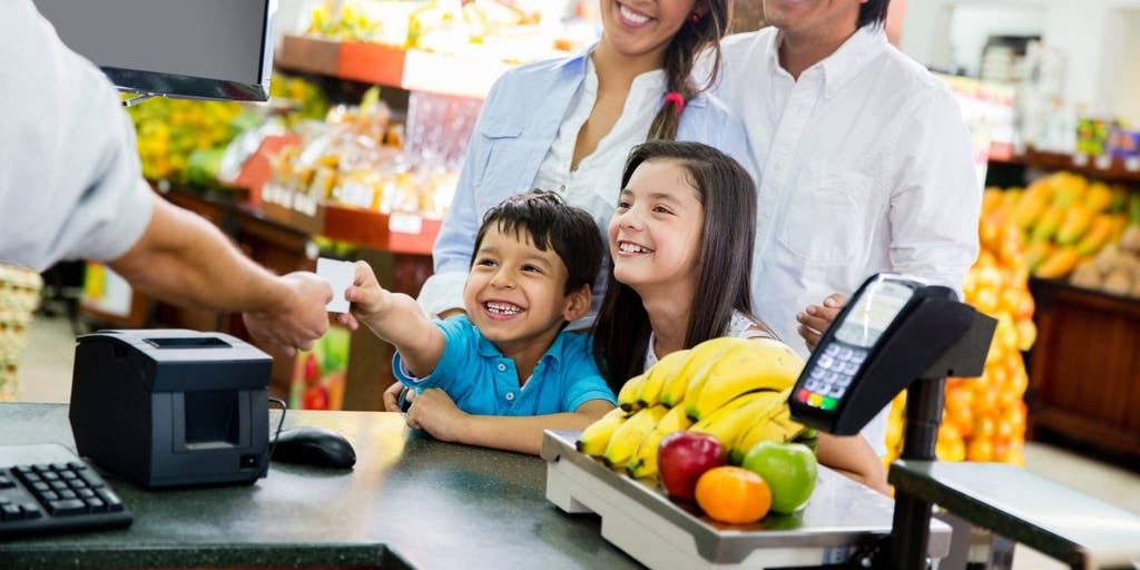 Family shopping and paying with a card