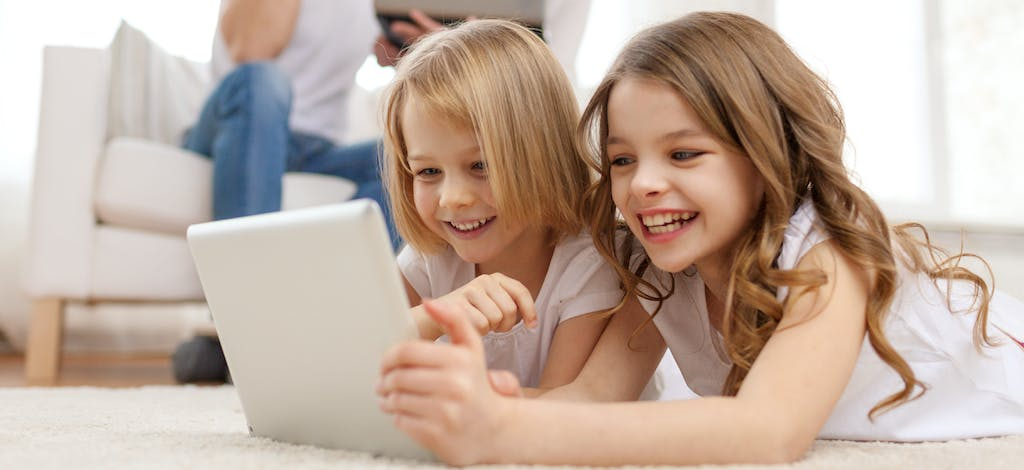 Image of 2 blond girls watching a screen