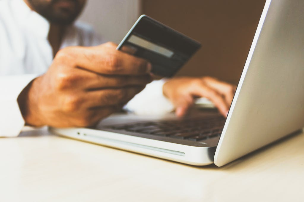 A picture of a man inputting his credit card details online.