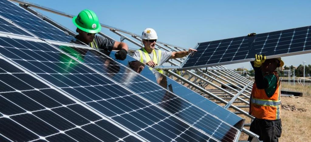 Three construction men working outside in the sun installing solar panels