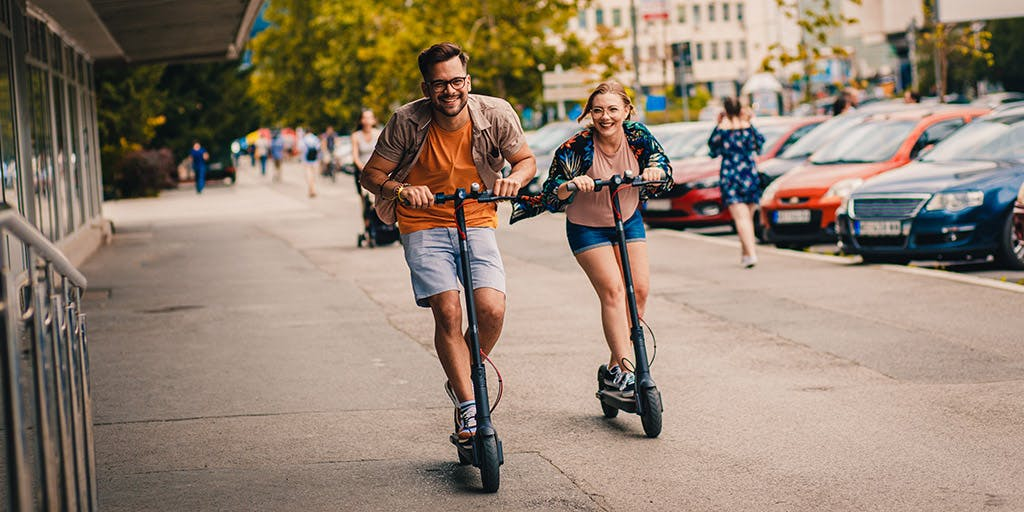 Young couple having fun driving electric scooters through the city.