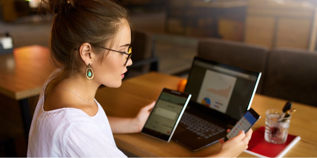 Image of woman working on her desk looking at iPad, laptop and smart phone